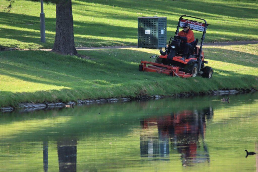 ride on lawn mower next to lake